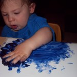 Sliding his hand back and forth in the paint.